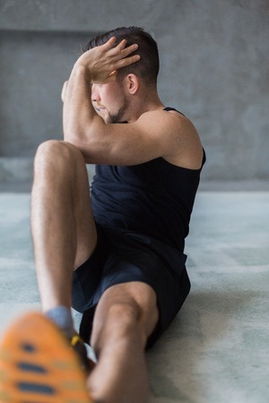Young man workout in fitness club. Closeup portrait of caucasian guy making exercise, sit-ups and cross crunches for abs muscles, training indoors. Vertical Stock Photo
