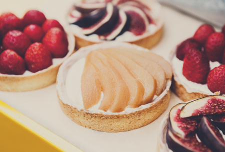 Fruit and berry tarts dessert tray assorted. Closeup of beautiful delicious pastry sweets with fresh natural pears. French Bakery catering. Filtered, shallow depth of field