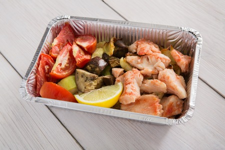 Healthy food background, take away of natural organic meals in foil container, closeup. Fitness nutrition, salmon fish and steamed vegetables. Restaurant dishes delivery