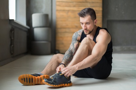 Little break. Handsome young man in sportswear relax after training in gym, sit on floor, lacing sneakers shoes. Sexy guy with tattoo in fitness center Stock Photo