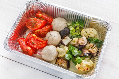 Healthy food background, take away of natural organic meals in foil container. Fitness nutrition, meatballs and steamed vegetables closeup. Restaurant dishes delivery