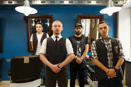 Young professional barbers team posing to camera inside modern barbershop. Four masculine male hairstylists standing indoors at workplace in hair salon Stock Photo