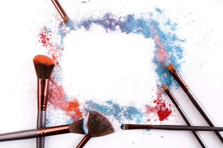 Makeup brushes frame with blush and eyeshadow of pink, blue and coral tones sprinkled on white. Make up and female cosmetics background Stock Photo