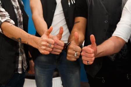 Welcome to our professional team. Close-up shot of young barbers posing to camera with thumb up gesture, inside modern barbershop. Four masculine male hairstylists at work place in hair salon Stock Photo