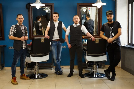 Team of young professional barbers posing to camera inside modern barbershop. Four masculine male hairstylists standing indoors at workplace in hair salon Stock Photo