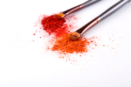 Makeup brushes with blush or eyeshadow of pink, red and coral tones sprinkled on white. Make up and female cosmetics background Stock Photo
