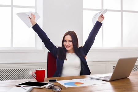 Sucessful project. Happy business woman sitting at table in office and keeping arms with documents outstretched , enjoying new achievement. Female manager having fun at workplace after working day Stock Photo
