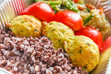 Healthy food delivery closeup diet concept. Take away of fitness meal. Weight loss lunch in foil boxes. Falafel with brown rice and vegetables on white wood Stock Photo
