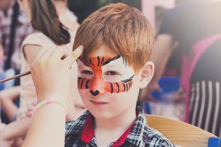 Kind met tiger gezicht schilderen. Kinderen vakantie, verjaardagsfeestje entertainment.