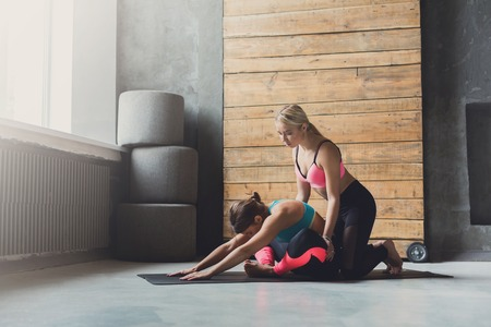 Yoga class instructor helps beginner to make asana exercises. Teacher assists to make cobbler pose, baddha konasana. Healthy lifestyle in fitness club. Stretching with coach Stock Photo