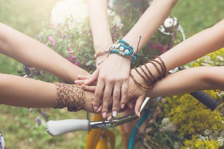 Mädchen Freundschaft. Vereinigte Hände von jungen Frauen. Stilvolle Freundinnen in den boho Hippiearmbändern nähern sich Fahrradlenkstange, Draufsicht. Gemeinsamkeit und Unterstützung, Jugendmode und aktive Freizeitgestaltung. Standard-Bild