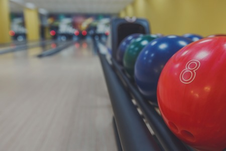 shiny floor: Bowling background. Interior of bowling alley lane with balls return machine closeup, selective focus on red ball