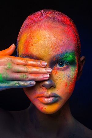 Holi colours festival. Portrait of beauty model with colorful powder make up posing to camera on dark studio background. Beautiful woman with rainbow makeup. Abstract colourful art make-up, crop