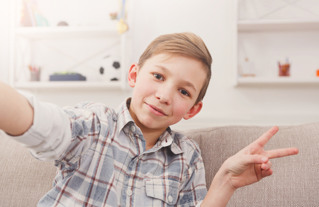 Happy child making selfie for social networks. Boy at home on sofa in living room