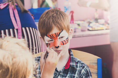 Children holiday, birthday party entertainment. Face art, tiger painting on boys face