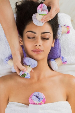 Herbal ball massage in ayurvedic spa. Female massagist with young woman in wellness center. Healthcare therapy to beautiful indian girl in beauty parlor, top view of face with eyes closed