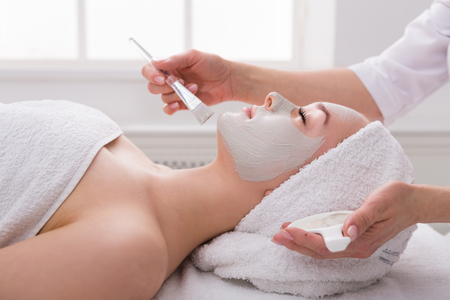 Face peeling mask, spa beauty treatment, skincare. Woman getting facial care by beautician at spa salon, side view, close-up Banco de Imagens