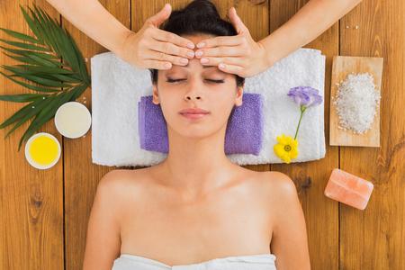 Kopfmassage im Spa. Junge Frau im Wellnesscenter Beruflicher Cosmetologist machen Verfahren zum schönen indischen Mädchen im Schönheitswohnzimmer. Draufsicht auf Holz mit Aromasalz und anderen Behandlungen Standard-Bild - 75186635