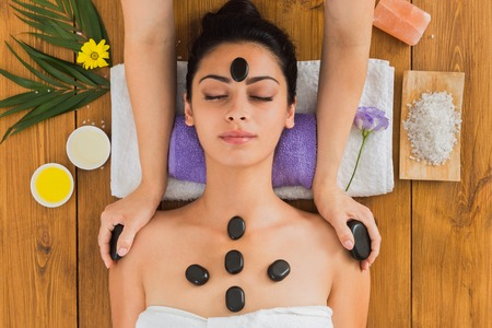warming therapy: Black marble stone massage in spa. Beautician with female patient in wellness center. Professional cosmetologist make relaxation procedure to beautiful indian girl in beauty parlor, top view on wood