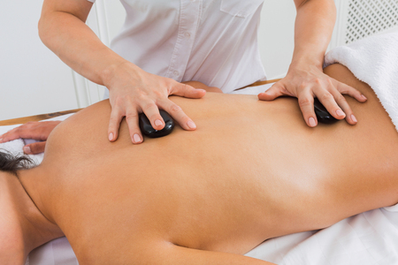 warming therapy: Black marble stone back massage in spa. Female beautician doctor with patient in wellness center. Professional massagist make relaxation procedure to beautiful indian girl in beauty parlor.