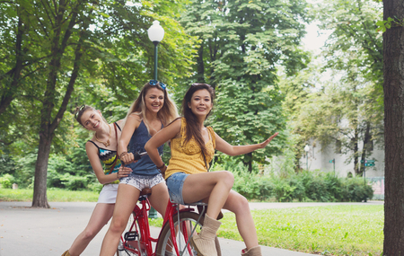 tonto: Ride bikes together in park, friends have fun on bicycles. Girls leisure Foto de archivo