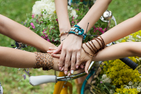 United hands of young females. Stylish girlfriends in boho hippie bracelets near bicycle handlebar, top view. Togetherness and support, youth fashion and active lesiure. Women friendship Stock Photo