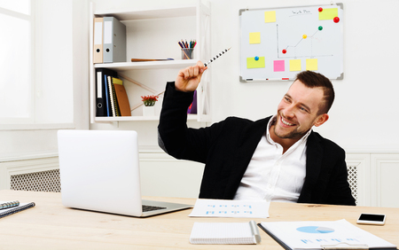 working attire: Working with fun. Smiling successful businessman in formal wear sitting at workplace in modern office and laughing Stock Photo