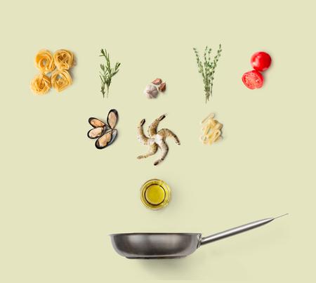 Italienisches Lebensmittel kochen, Meeresfrüchteteigwaren, lokalisiert auf gelbem Hintergrund. Frutti di Mare mit Fettuccine-Spaghetti. Muscheln, Garnelen, Garnelen, Calamari-Ringe und andere Zutaten über der Pfanne
