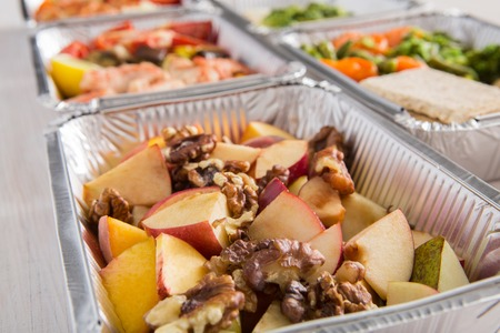 Healthy food background. Take away of natural organic meals in foil boxes. Fitness nutrition. Restaurant dishes delivery