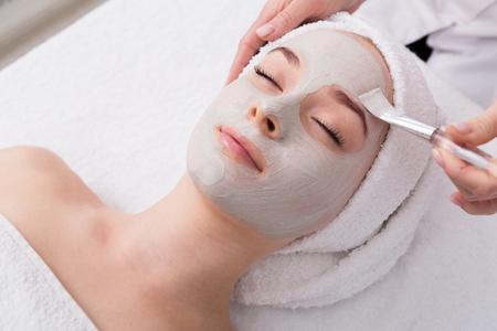 Máscara de descamação facial, tratamento de beleza de spa, cuidados com a pele. Mulher recebendo cuidados faciais por esteticista no salão de spa, vista lateral, close-up