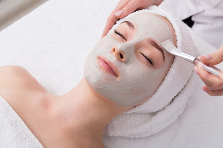 Face peeling mask, spa beauty treatment, skincare. Woman getting facial care by beautician at spa salon, side view, close-up Archivio Fotografico
