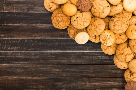 Cookies and sweet biscuits at dark natural wood, background with copy space. Oatmeal and chocolate drops border, dessert for tea. Stock Photo