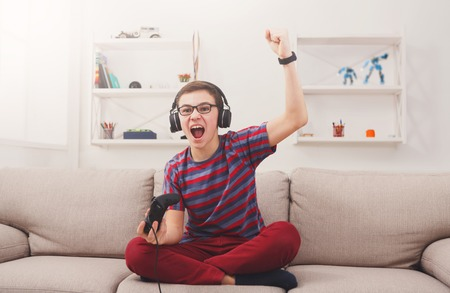 Gaming video games concept - excited teenage boy playing football game with joystick and headphones, enjoying win while sitting on sofa in living room at home