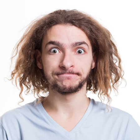 astonishing: Portrait of man with surprised facial expression looking at camera while standing on white isolated studio background