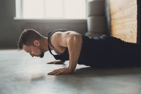 Young man workout in fitness club. Profile portrait of caucasian guy making plank or push ups exercise, training indoors Stock Photo