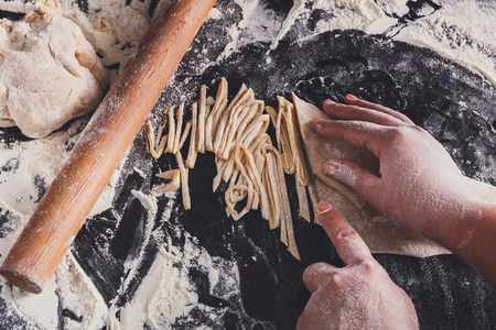 sprinkled: Cutting homemade noodles on black background, sprinkled wheat flour and raw pasta. Cooking dough