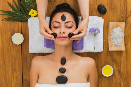 warming therapy: Black marble stone face massage in aroma spa. Beautician with female patient in wellness center. Professional therapy, relaxation procedure to beautiful indian girl in beauty parlor, top view on wood