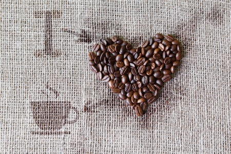 I love coffee. Burlap texture with coffee beans heart shape background, love symbol with cup and arrows. Sack cloth canvas and seeds at hessian textile Stock Photo