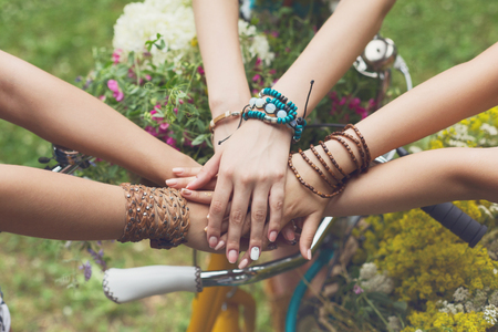 Girl Friendship. United hands of young females. Stylish girlfriends in boho hippie bracelets near bicycle handlebar, top view.