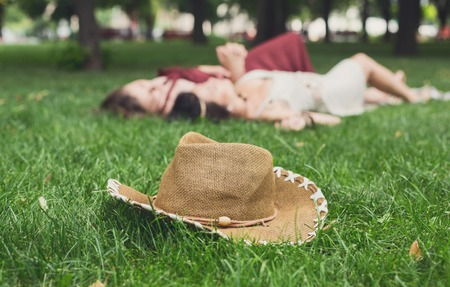 retro woman: Girls unfocused relax in summer park, young hippie friends leisure. Focus on hat