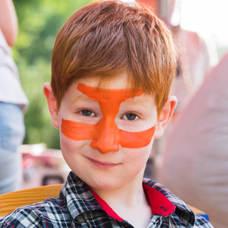 Children holiday, birthday party entertainment. Face art, tiger painting on boys face Stock Photo