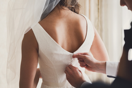 get dressed: Bridal morning, bride wears dress. Groom helping fiancee to get dressed, adjusting buttons on wedding gown, rear view. close-up, crop