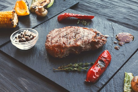 Grilled beef steak cooked on barbecue, closeup on dark wooden table background. Fresh juicy roasted red meat on black stone board, pepper and rosemary. Restaurant food, delicious dish, selective focus Stock Photo