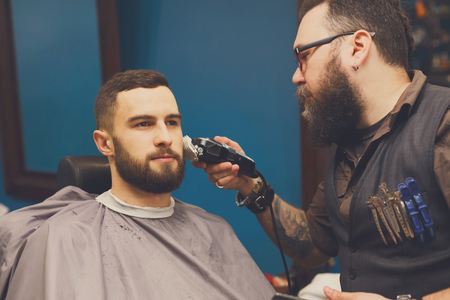 haircut: Barber styling beard with trimmer at barbershop. Stylish hairdresser in male hair salon
