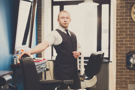 haircut: Young elegant barber waits for client, looking at camera. Male hairstylist in barbershop
