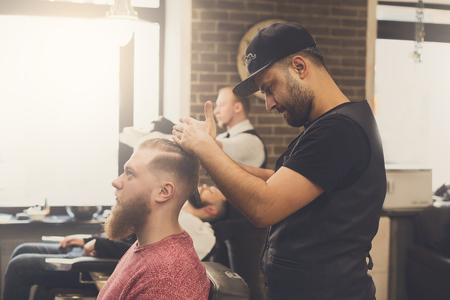 haircut: Male barbershop candid image. Styling beard to client. Stylish hairdressers in men hair salon