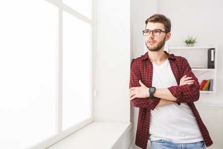 ambitious: Thoughts about success. Confident businessman in casual standing at office workplace and looking through window Stock Photo