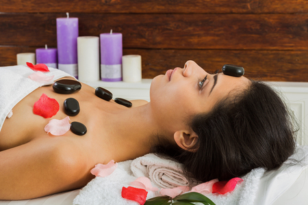 warming therapy: Black marble stone hot massage in spa. Female patient in wellness center. Relaxation procedure to beautiful indian girl in beauty parlor, woman lays on bed with rose petals