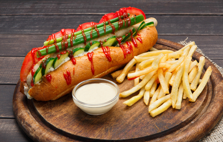 Hot dog and french fries. American fast food restaurant cuisine - hotdog with celery, cucumbers, mayonnaise and ketchup and heap of potato chips at wooden desk on table.