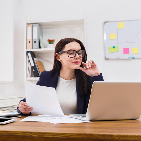 Succesfull woman, female carreer concept. Beautiful young businesswoman sitting by wooden desk with laptop. Modern office worker in white room interior. Stock Photo